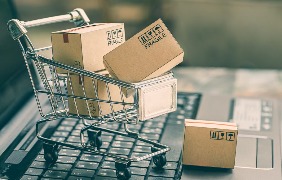 Miniature shopping cart with boxes on a laptop