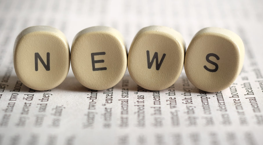 "Round ivories with letters on them spell out ""NEWS"", sitting on a newspaper"