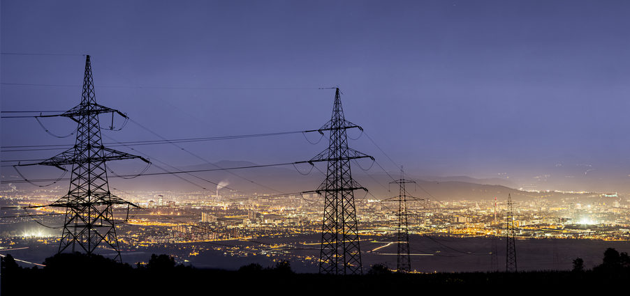 Electrical towers at dawn above a city