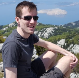 Picture of Seth Duda, sitting on rock above mountain lake