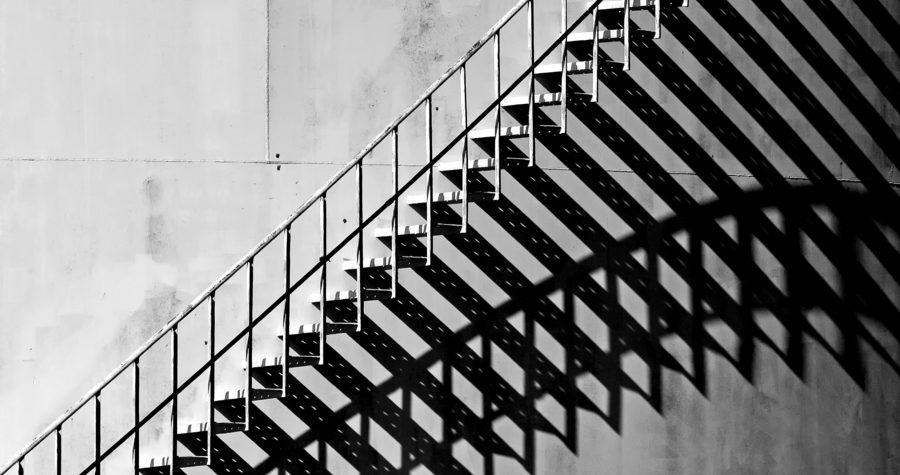 Heavy shadow of stairway on old white storage tank. Stairs cast interesting shadows in the late afternoon Sunlight. Black and White