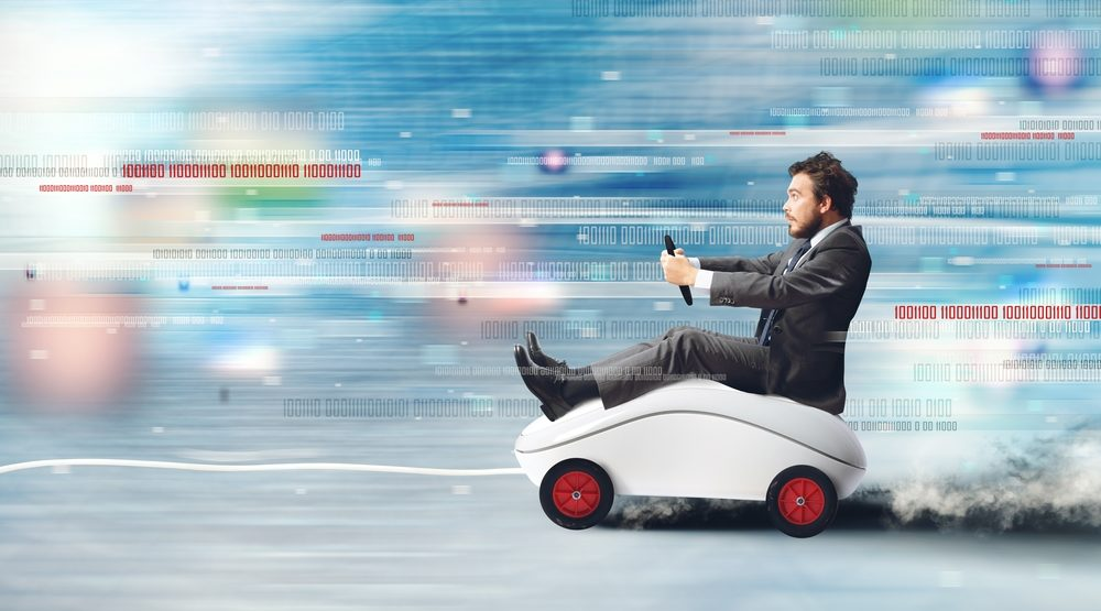 Composite image of businessman riding a speeding car, shaped like a mouse. Concept of fast internet with running mouse