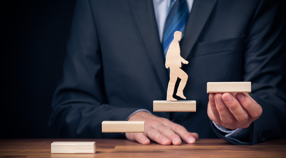 Man in business suit holding floating stairs, cutout of man walking up stairs