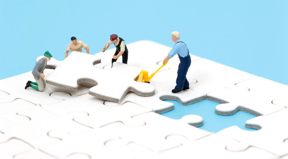 Group of miniature people assembling jigsaw puzzle, team support and help concept. Business teamwork concept.