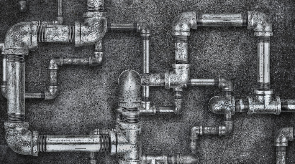 Complicated arrangement of plumbing pipes. Black and white image.