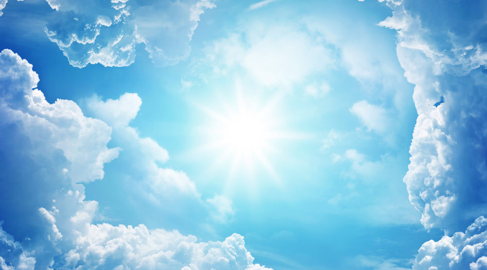 Sun centered in cicle of fluffy white clouds in a blue sky.