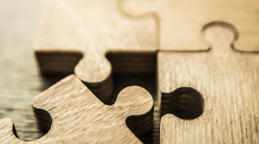 Incomplete puzzles on wooden table background. closeup. Puzzles on wooden table, close up.