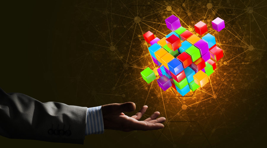 Close-up of businessman hand holding cube figure as symbol of innovation. 3D rendering.