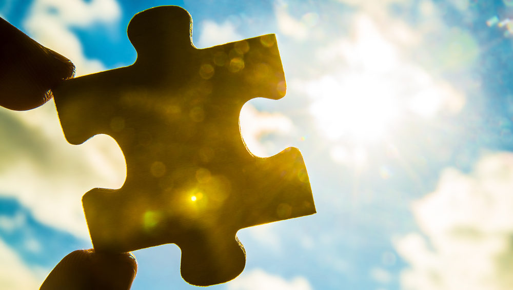 Hand holding puzzle piece against sky, sun rays and clouds.