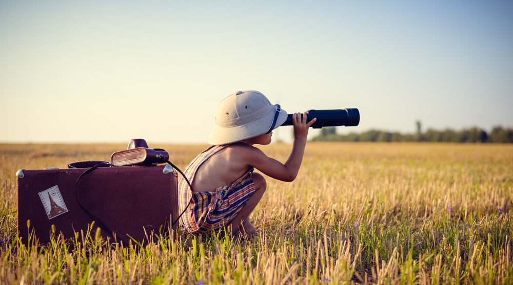 Picture of boy wearing pith helmet and plaid romper looking in spyglass in wheat field. Little explorer with camerabag and old suitcase on sunny countryside background.